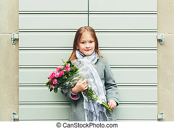 Outdoor portrait of 5-6 year old little girl wearing grey...