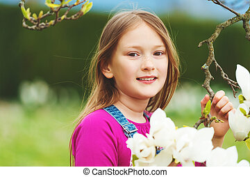 Spring portrait of 7-8 year old pretty little girl with...