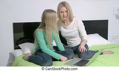 Attractive young family or mother and daughter using a laptop to make future plans