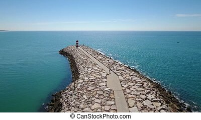 Aerial. Breakwater wharf, the fishing town of Quarteira port...