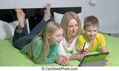 Happy family at home using a tablet to shopping online.