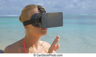 Woman using VR-headset on the beach - Young woman in...