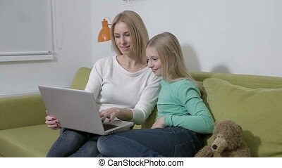 slowmotion - Attractive young family or mother and daughter using a laptop to make future plans
