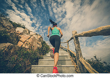 young fitness woman running on mountain stairs