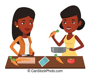 Women cooking healthy vegetable meal. - African young women...