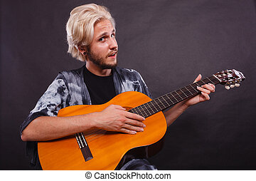 Blonde man playing acoustic guitar - Music, passion concept....