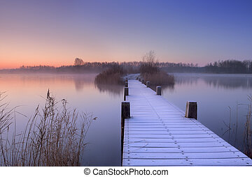 Boardwalk on a lake at dawn in winter, The Netherlands - A...