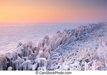 Sunrise over a frozen lake in The Netherlands - Sunrise over...