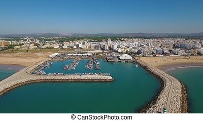 Aerial. Fishing port Quarteira with breakwaters, filmed from...