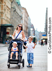 Mother and two kids walking in city center - Vertical photo...
