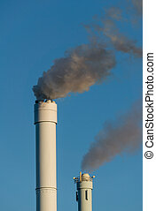 polluted smoke against a clear blue sky from the tall...