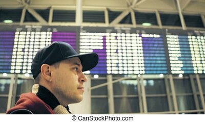 Caucasian man wearing cap walks near airport departure...