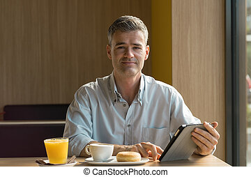Businessman having breakfast at the bar, he is using a...