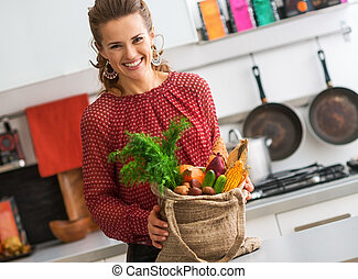 happy young housewife with local market purchases in kitchen