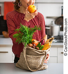 Young housewife with purchases from local market eating...