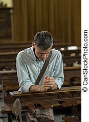 Religious man in the Church - Religious man kneeling at the...