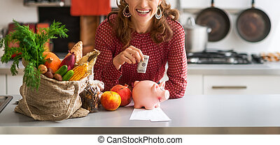Closeup on happy young housewife putting money into piggy...
