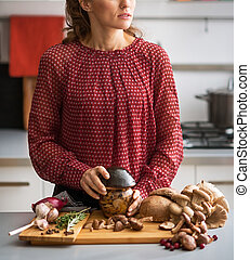 Pensive woman holding a jar of mushrooms in kitchen