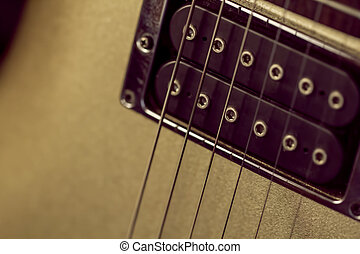Soft image of a black humbucking pickup on a gold guitar....