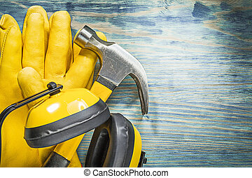Set of protective workwear claw hammer on wooden board...