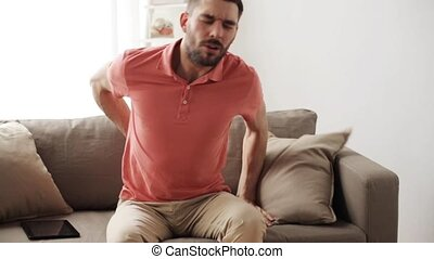 unhappy man suffering from backache at home - people,...