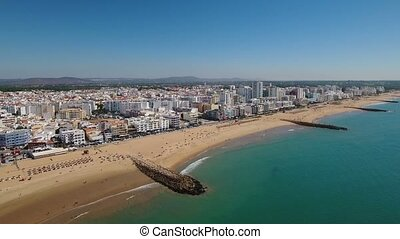 Aerial. Breakwaters and Quarteira beach filmed from the sky....