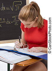 Caucasian schoolgirl by desk studying math exam - High...
