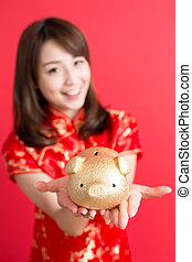 beauty woman wear cheongsam and show gold piggy bank to you...