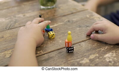 Child playing with dice and counters - Close-up shot of...