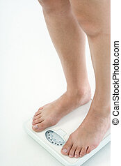 Overweight woman legs standing on bathroom scales - Leg of...