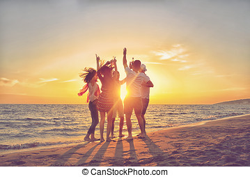 group of happy young people dancing at the beach on...
