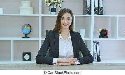 Smiling mature professional businesswoman in casual, with arms crossed standing in office. Shallow focus