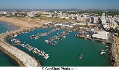 Aerial. Fishing port and moored ships town Quarteira....