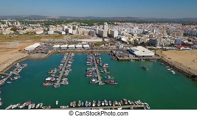 Aerial. Ships moored in the fishing town of Quarteira. Video from the sky.