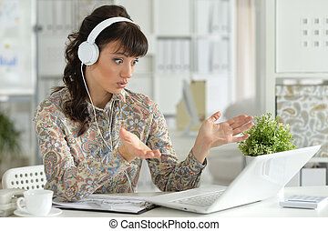 Young businesswoman with headphones sitting at the table and...
