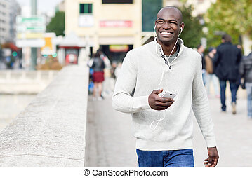 Black young man with a smartphone in his hand in urban...