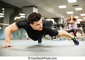 Attractive man doin pushups in the gym - Attractive man...