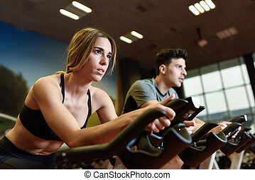 Couple in a spinning class wearing sportswear. - Attractive...