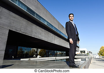 Young businessman wearing blue suit and tie in urban...