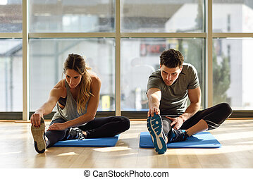 Two people streching their legs in gym. - Young woman and...