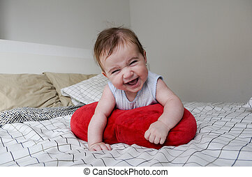 Baby girl lying on her parents bed with funny expression