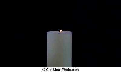 White candle is extinguished on a black background