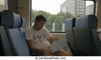 Man in train entertaining with laptop
