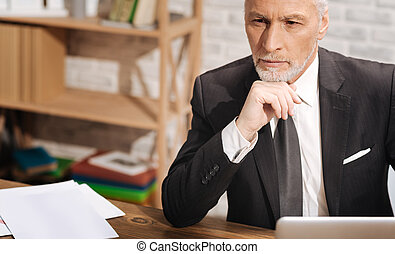 Thoughtful handsome businessman considering new strategies -...