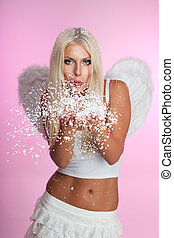 Angel blow off snow from her hands with wings on pink
