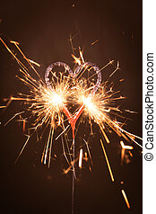 Burning sparkler in heart shape against black background