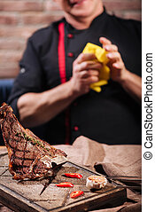 Close up of steak and a man standing in restaurant