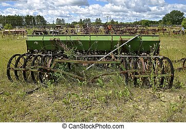 Old grain drill - An old green vintage grain seed drill left...