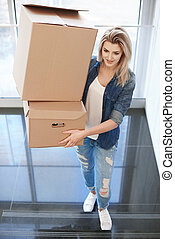 Woman carrying cardboard box upstairs