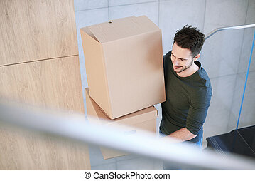 Man smiling and carrying moving box indoors